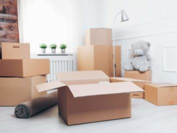 Room with moving boxes in the foreground and a grey soft toy bear in the background